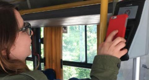 Mujer pagando el pasaje de micro con aplicación de everis